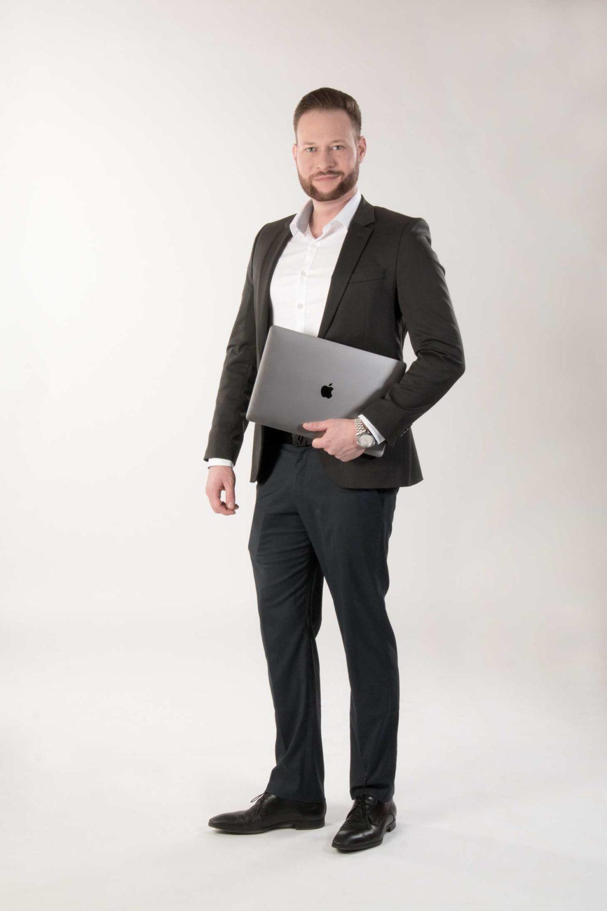 Webdesign und Marketing Niklas Hornig steht am Laptop Ganzkörper